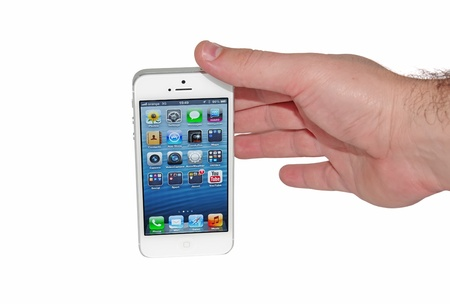 Piatra Neamt, Romania - December 03, 2012: Hand taking the new Apple iPhone 5 with on a white background