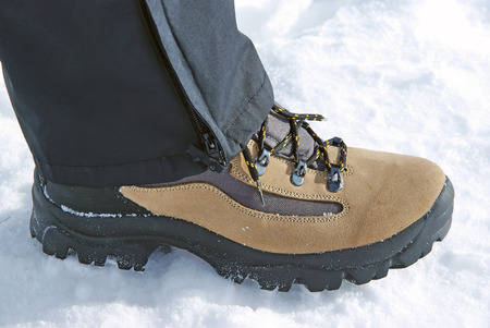 Leather boot with black laces on snow. Stock Photo