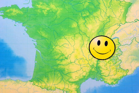 Yellow happy face on France map, close up image. photo