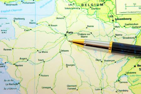 Pen indicating Paris city on France map. photo