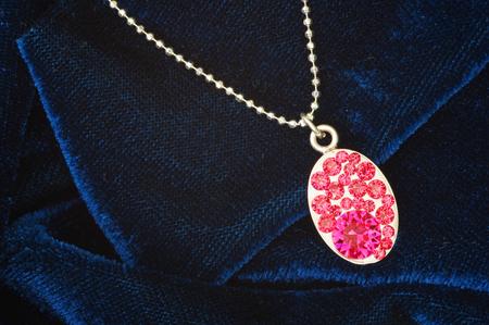 blue velvet: Pink stones on pendant over blue velvet Stock Photo