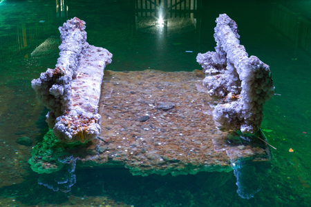 Crystallized Salt bench in Underground lake. Lake is located at a depth of 35 meters underground, dug manually by miners. Stock Photo