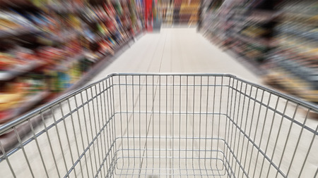 Shopping cart and motion blur in supermarket aisle