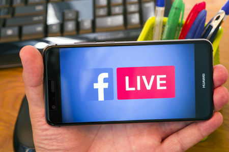 PIATRA NEAMT, ROMANIA - JULY 30, 2018: Hand holds a mobile phone with Facebook Live logo on the screen, office background.