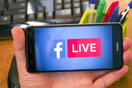 PIATRA NEAMT, Rumania - 30 de julio de 2018: Mano sostiene un teléfono móvil con el logo de Facebook Live en la pantalla, fondo de la oficina. Editorial