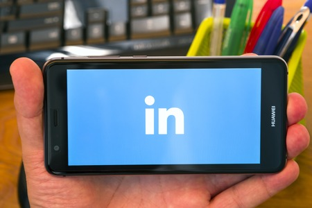 PIATRA NEAMT, ROMANIA - JULY 30, 2018: Hand holds a mobile phone with Linkedin logo on the screen, office background.