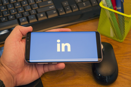 PIATRA NEAMT, ROMANIA - JULY 30, 2018: Hand holds a Samsung S8+ with Linkedin logo on the screen, office background.