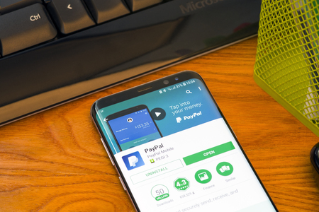 PIATRA NEAMT, ROMANIA - JULY 30, 2018: Samsung S8+ with Google Play store, Paypal  application, office background. Editorial