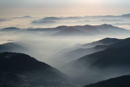 Winter landscape, crest over crest with low clouds, Romanian Carpathians. Standard-Bild
