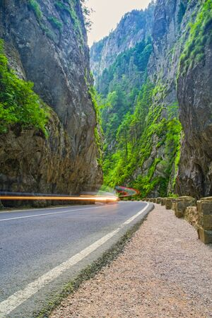 Summer canyon road, Bicazului Gorges in Romania, mountain road near rock wall