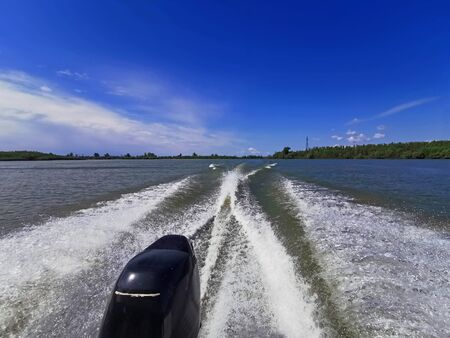 Wake leads water behind a speeding boat in a sunny day