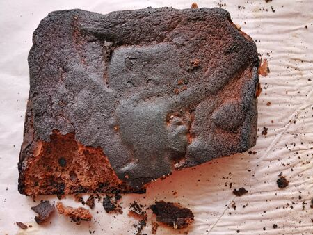 Close image of over burned pie on baking paper, cooking error cake