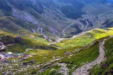 Foot path and windingTransfagarasan road in Romanian Carpathians. Archivio Fotografico - 129469143