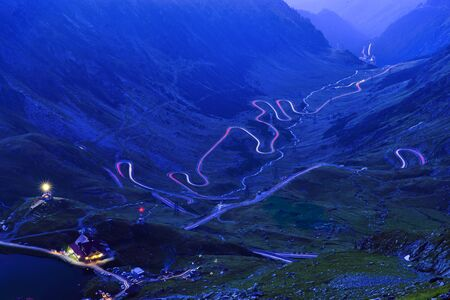 Long exposure mountain scene, car lights on curvy road. Balea Lake and Transfagarasan road in Romania 写真素材