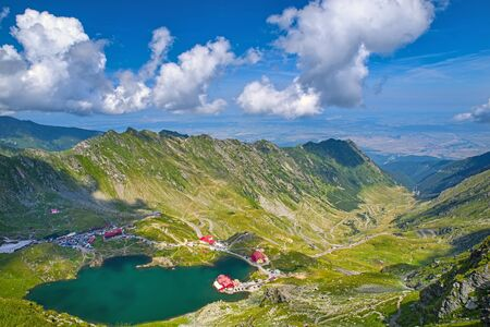 Balea lake and Transfagarasan road seen from above in the summer, landscape in Romanian Carpathians, Fagaras rocky mountains Archivio Fotografico - 129468976