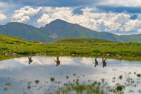 Summer mountain landscape, reflecting tourists in water, trekking travel concept
