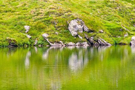 Summer rocky lake mirroring on the mountain, Romanian Carpathians