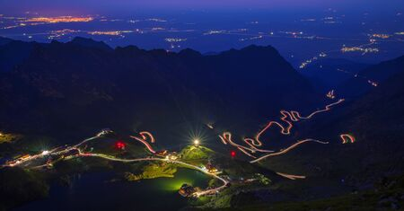 Long exposure on summer mountain, Balea Lake, winding road of Transfagarasan and valley lights 写真素材