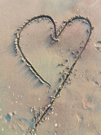 Drawing love symbol in sandy beach Banque d'images - 129468504