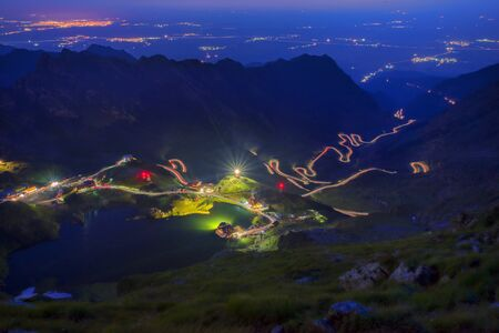 Night mountain landscape: winding road and glacier lake in Romanian Carpathians, Balea lake touristic destination 写真素材