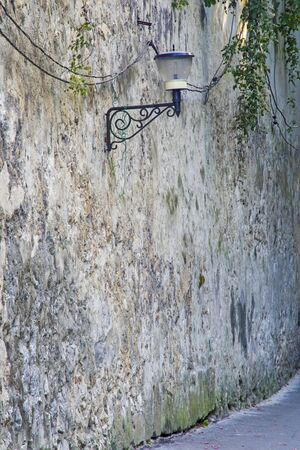 Street lamp on ancient wall in Brasov, Romania, aged fortress brick wall