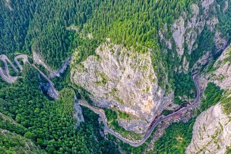 Above view of winding forest road, mountain pass in Romanian Carpathians Фото со стока