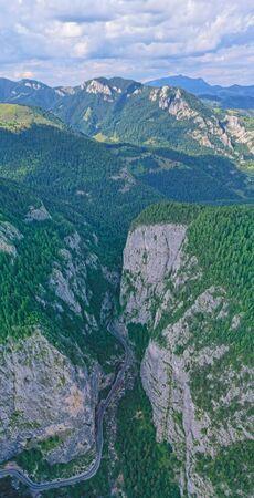 Rocky mountain pass in Romanian Carpathians, highway road between huge rocks, aerial mountain view Фото со стока
