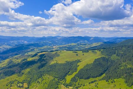 Mountain pasture and green forest in aerial landscape