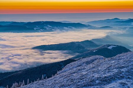 Winter sunrise from mountain top,mist in the valley in Romanian Carpathians.