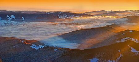 Winter sunrise panorama from the summit in Romanian Carpathians; misty valley and sun rays.