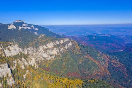 Aerial view of rocky mountain and autumn forest bellow, Romanian Carpathians