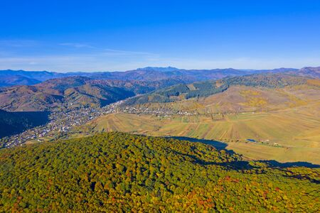Aerial autumn landscape; forest, fields and rural village, Romanian Carpathians. Stok Fotoğraf