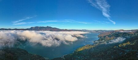 Mist cloud panorama, aerial view of mountain lake covered by mist cloud in Romanian Carpathians, autumn landscape.