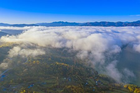 Mist clouds over the village and forest, aerial autumn landscape in Romanian Carpathians. 版權商用圖片