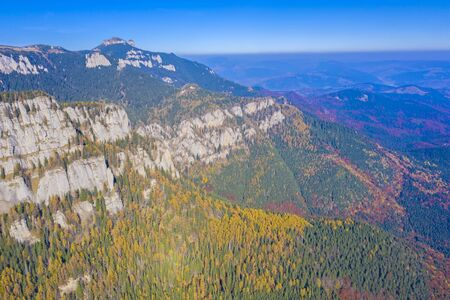 Autumn rocky mountain viewed from above in Romanian Carpathians, aerial view of Ceahlau mountain, beautiful colored forest