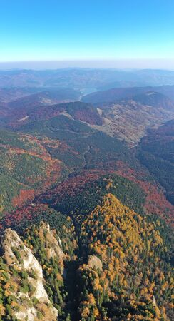 Aerial view of autumn forest trees and mountain rock in Romanian Carpathians. 스톡 콘텐츠