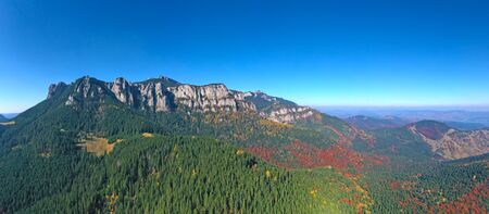 Aerial view of rocky mountain and colored forest in Romanian Carpathians, beautiful autumn landscape 스톡 콘텐츠