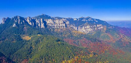 Aerial view of rocky mountain and colored forest in Romanian Carpathians, beautiful autumn landscape with blue sky.
