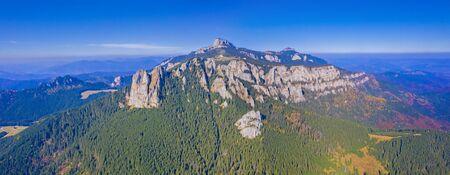 Aerial autumn landscape in Romanian Carpathians, rocky mountain and autumn forest landscape