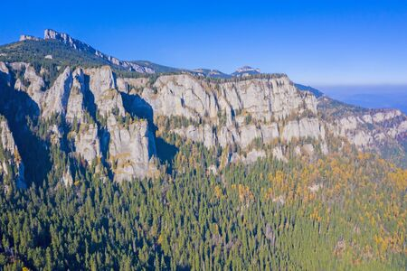 Aerial view of mountain rock wall and autumn forest in Romanian Carpathians. 스톡 콘텐츠