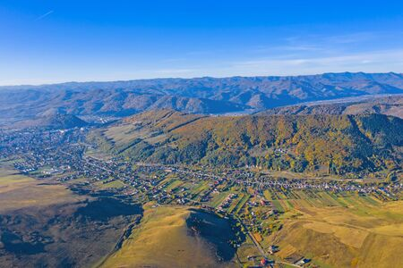 Aerial view of a rural landscape in autumn: village and forest in Romanian Carpathians. 스톡 콘텐츠