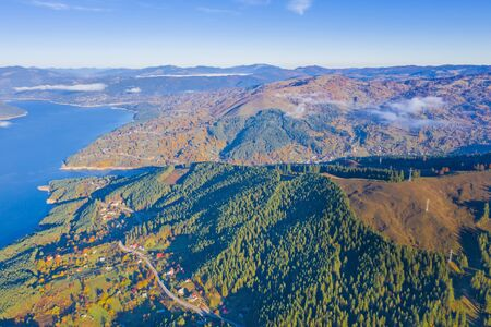 Autumn aerial view of mountain lake and villages from the valley in Romanian Carpathians, Bicaz Lake