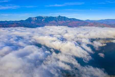 Flying over mist clouds in Romanian Carpathians. clouds over the lake and autumn mountain view