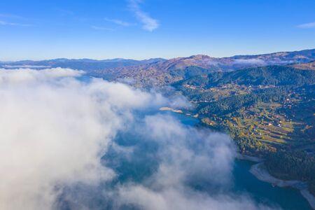 Mist cloud over the lake from above, autumn mountain landscape in Romanian Carpathians, Bicaz Lake.