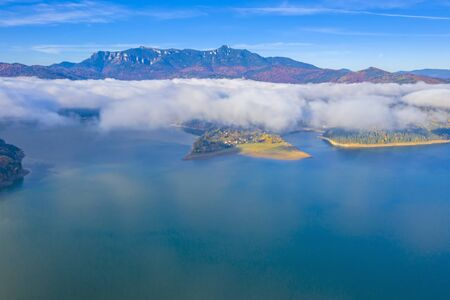 Aerial view of mist over mountain lake  and autumn forest, Romanian Carpathians scene, Bicaz Lake