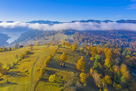 Aerial view of autumn hill and forest with cloud floating over the lake in Romanian Carpathians