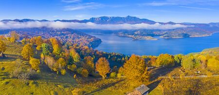 Autumn mountain panorama in Romanian Carpathians, mist cloud over the lake and colored trees, Bicaz Lake