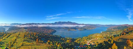 Aerial view of autumn mountain panorama in Romanian Carpathians mist layer over the lake and colored forest.