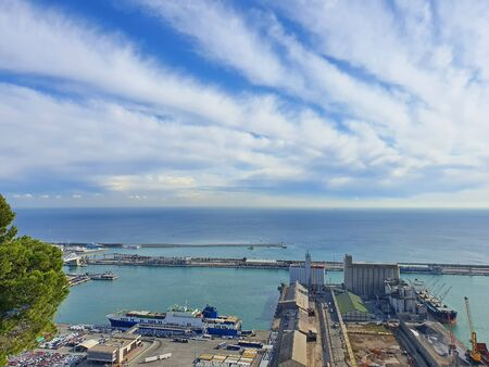 Aerial view from Montjuic Hill over industrial port of Barcelona, docked ships, cranes and containers Banco de Imagens