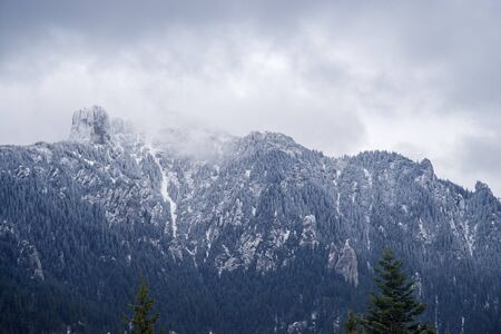 New snow cover on mountain summit, white rocky mountain in Romanian Carpathians. 免版税图像
